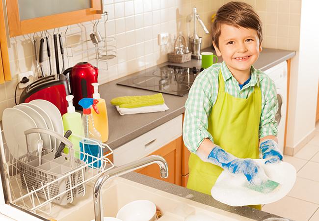 niño lavando platos