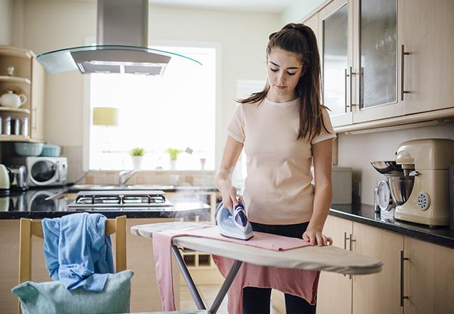 adolescente planchando en su casa